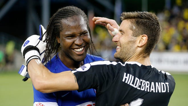 FC Cincinnati Djiby Fall (9) and Mitch Hildebrandt (1) celebrate on the field after the second half of the US Open Cup soccer match between FC Cincinnati and Columbus Crew at at Nippert Stadium on June 14, 2017.
