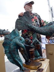 Artist Ron Lemoine stands with a couple of his sculptures Saturday during the Melbourne Art Festival.