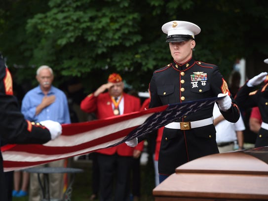 Marines fold a flag during an honor guard ceremony
