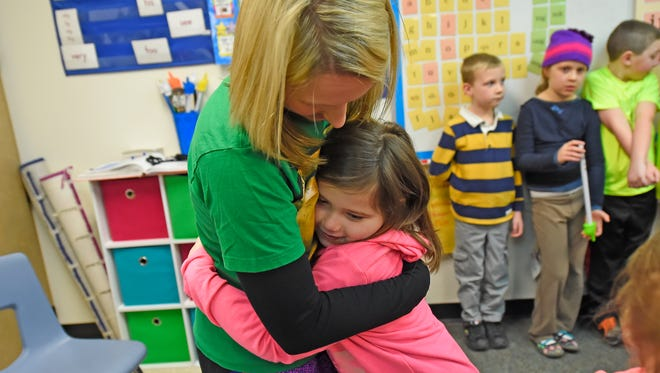 Golden Apple award-winning teacher Brittany Zellmer gets a hug after being presented with the award in her first-grade class at Westwood Elementary School in the De Pere School District on March 2.