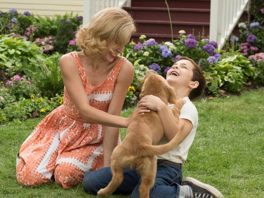 Juliet Rylance and Bryce Gheisar play with the dog