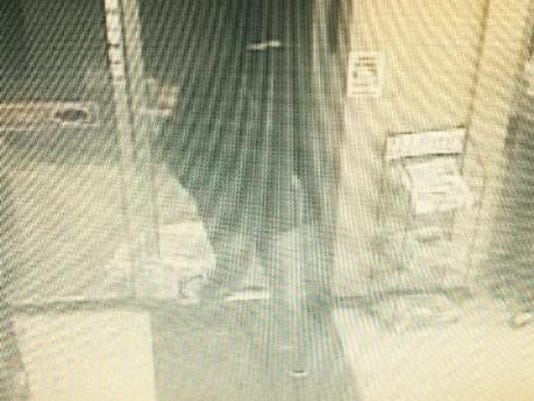 The suspect of a convenience store robbery is seen in a security camera still.