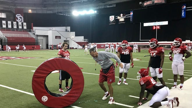South Dakota head football coach Bob Nielson demonstrated a blocking drill to Coyote running backs on Tuesday morning.