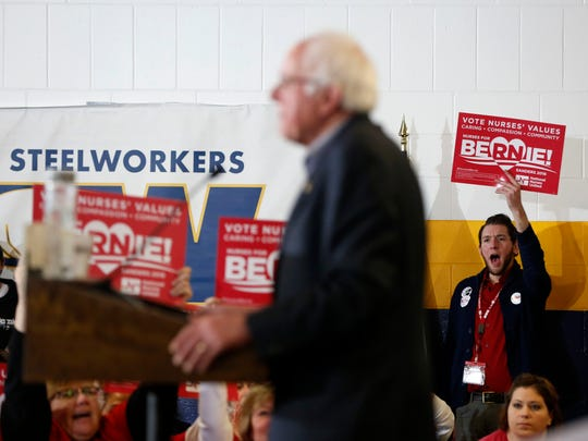 A supporter with National Nurses United waves a sign as Democratic presidential candidate Bernie Sanders speaks to the crowd at 10:55 a.m. Tuesday, Jan 26, 2016, at the United Steelworkers Local 310L Union Hall in Des Moines.