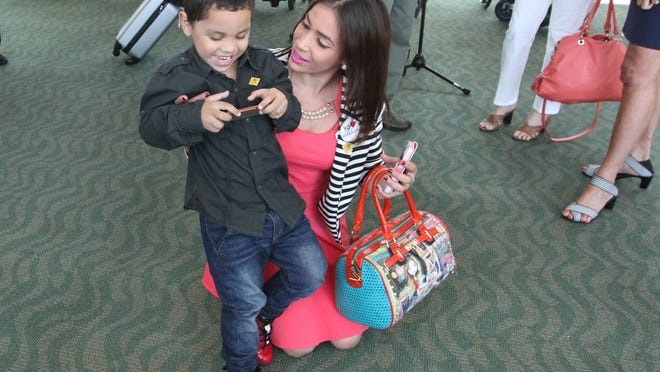 Angel Vicente, 4, and Andelina Tejada spend time together at gate D4 while awaiting their flight to San Juan, Puerto Rico on Sunday.