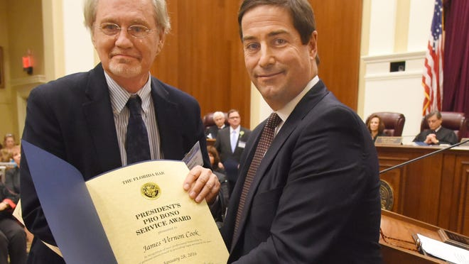 James V. Cook, left, a lawyer from Tallahassee, receives The Florida Bar President's Pro Bono Service Award for the 2nd Judicial Circuit from bar President Ramón A. Abadin.
