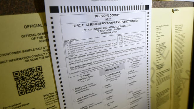An absentee ballot hangs on a bulletin board in a Board of Elections office.