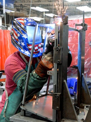 Jimi Dao welds on the supports for an industrial sized lawn mower screen inside HUI Manufacturing in Kiel on Thursday, Dec. 18, 2014.