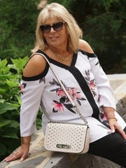 Lisa McInnis wears a floral print cold-shoulder top by Alfani; black skinny pants from Chico's, and bronze shoes by Franco Sarto.
