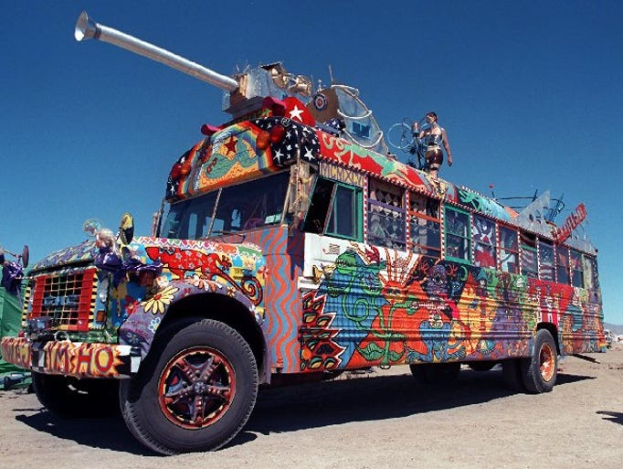 Kathy Prout of Santa Cruz, Calif. dances on top of a bus to the amusement of onlookers at the Burning Man Celebration at Fly Ranch on Thursday afternoon on August 28, 1997.