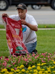 John Dobat, of Columbus Township, spreads a bag of mulch Saturday at Pine Grove Park in Port Huron. Volunteers planted nearly 200 flats of flowers in the park.