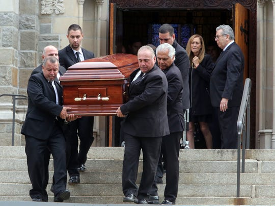 The casket is removed from the church during Robby Schartner's funeral at the Church of the Resurrection in Rye.