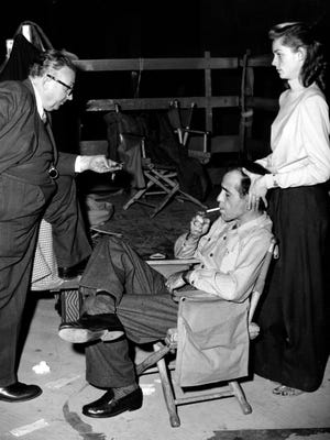 """Actor Humphrey Bogart, lighting cigarette, actress Lauren Bacall, massaging her husband's head, and cameraman Karl Freund relax on the set of """"Key Largo"""" in Hollywood on Jan. 19, 1948."""