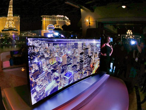 A model stands next to a Samsung 105-inch UHD curved TV during a preview event for the International Consumer Electronics Show in Las Vegas.