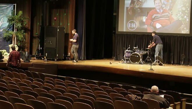 Tech crew members help to set up the stage in the Saline Middle School auditorium for Sunday services for the NorthRidge Church. NorthRidge is not your ordinary church, it is a portable one.