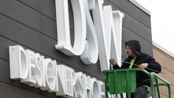 Bryant Lucus, of the Lititz Sign Co., installs a new sign at a new DSW Inc. location at the West Manchester Town Center.