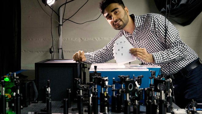 Barmak Heshmat poses with his prototype scanning device in a lab at Massachusetts Institute of Technology in Cambridge, Mass.