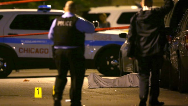 In this Monday, May 30, 2016 file photo, police work the scene where a man was fatally shot in the chest in Chicago's Washington Park neighborhood.