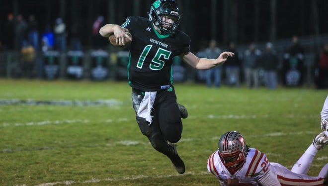 Mountain Heritage quarterback Trey Robinson lunges past Hendersonville's Ty'rese Hunt during the Nov. 24 playoff game at Mountain Heritage. Mountain Heritage took the win with a final score of 30-20.