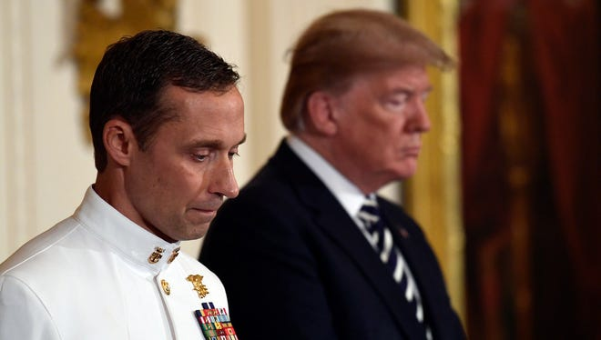 President Trump stands with Master Chief Special Warfare Operator Britt Slabinski during a ceremony to award him the Medal of Honor in the East Room of the White House.