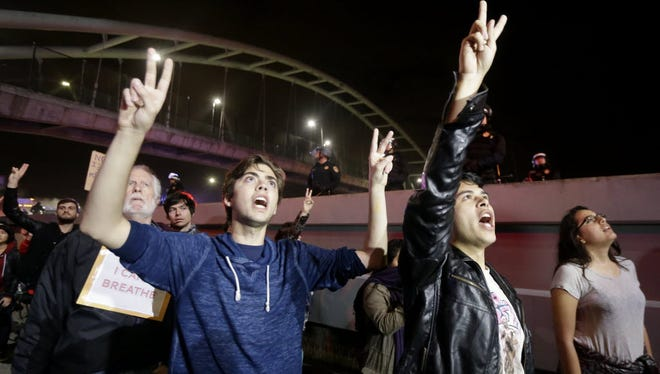 """Protesters raise their hands as they chant """"Hands Up Don't Shoot"""" under Highway 80 during a protest in response to police killings in Missouri and New York in Berkeley, Calif., Monday, Dec. 8, 2014."""
