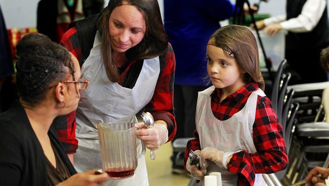 Nicole Hughes (center) and her daughter Olivia Uttech, 7, spend time with a guest at a Thanksgiving meal gathering at St. Vincent de Paul Society on the south side. Hughes and her daughter were among the three dozen volunteers who were on hand serving meals.