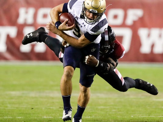 Navy quarterback Zach Abey runs with the football against Temple defensive lineman Jacob Martin during the first quarter of an NCAA college football game Thursday, Nov. 2, 2017, in Philadelphia. (Yong Kim/The Philadelphia Inquirer via AP)