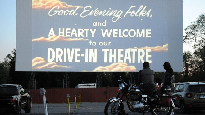 """Ryan Hayward, of Halifax, sits on his Royal Enfield motorcycle as he settles in to watch """"Raiders of the Lost Ark,"""" at the Wellfleet Drive-In, one of the last standing drive-ins in the region.   Merrily Cassidy/Cape Cod Times"""
