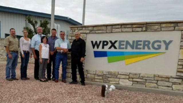 From left, Russ Knight, Heather Riley, Bryan Sanders, Andrea Felix, Robert Jordan, Randy VanDenBerg and Herb Stinson pose for a photo outside WPX Energy. The company recently donated $10,000 to the Aztec High School wrestling program's building fund.