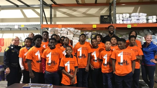 Michael Johnson spearheaded a campaign joining kids in the community with police officers in a community service effort.