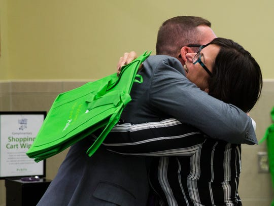 Trenton Thompson, store manager, hugs Angie Torres,