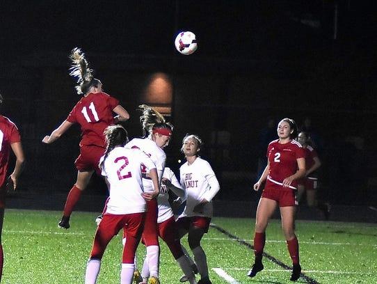 Anna Podojil (11) pops a header toward the goal for