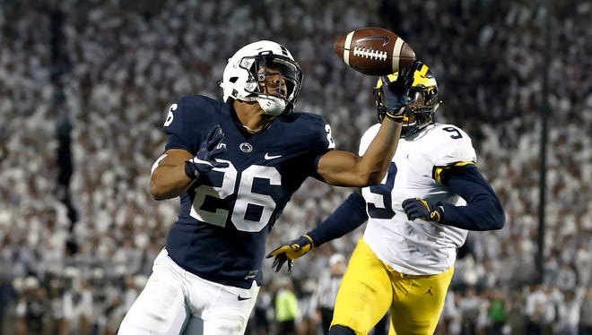 Penn State's Saquon Barkley (26) gains control of a pass and takes it in for a touchdown against Michigan during the second half on Saturday, October 21, 2017 at Beaver Stadium in University Park, Pa.