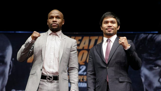 Floyd Mayweather Jr., left, and Manny Pacquiao pose for photos after a news conference, Wednesday, March 11, 2015, in Los Angeles. The two are scheduled to fight in Las Vegas on May 2.