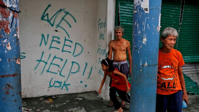 Residents stand next to grafitti requesting aid in the aftermath of Typhoon Haiyan. As many as 10,000 people are feared dead in the strongest typhoon to hit the Philippines this year.