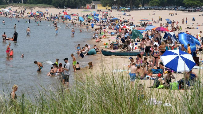 Swimmers and sunbathers at enjoy at day at the beach on Lake Michigan at Ludington on Thursday, July 5, 2018.