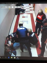 Medics can be seen through a video feed of a hallway
