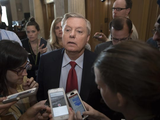 FILE - In this July 27, 2017 file photo, Sen. Lindsey Graham, R-S.C. is surrounded by reporters on Capitol Hill in Washington. Graham says President Donald Trump's comments about the violence in Charlottesville, Virginia, are dividing Americans instead of healing them. (AP Photo/J. Scott Applewhite, File)