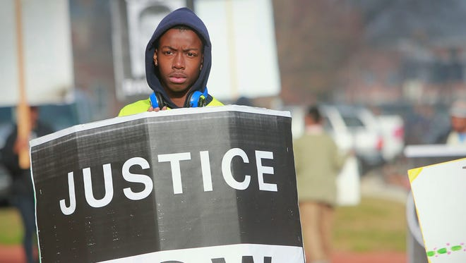 Dover high school student, Tayshaun Chisholm, 16, protests in front the Kent County Courthouse while the jury deliberates the case of Cpl. Thomas Webster IV on Monday.