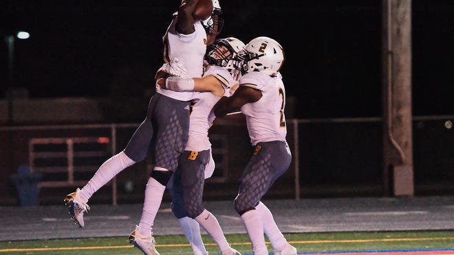 Battle's Manny Chiteri (10) jumps into the air, celebrating a touchdown as teammates Tommy Atherton (23) and Gerry Marteen Jr. (2) hug him in the end zone during a game Friday night at Moberly High School.