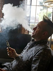 Geoff Braithwaite, owner of Tasty Vapor, exhales vapor