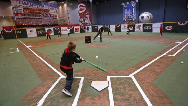 Charlie Thiemann, of Villa Hills, takes a hack on the Reds Field of Dreams at the 2013 Redsfest at the Duke Energy Convention Center.