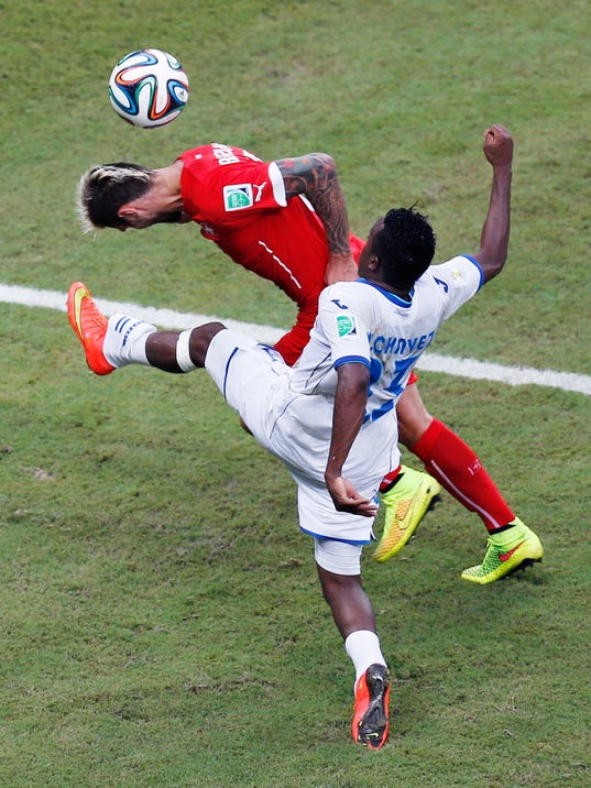 Honduras' Marvin Chavez battles Switzerland's Mario Gavranovic during the group E World Cup soccer match between Honduras and Switzerland at the Arena da Amazonia in Manaus, Brazil, Wednesday, June 25, 2014. (AP Photo/Frank Augstein)