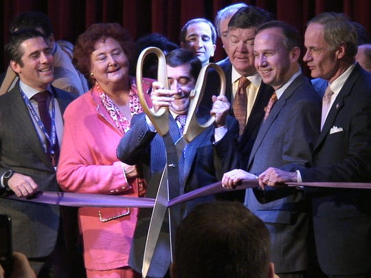 World Cafe Live founder Hal Real (center) cuts the ribbon surrounded by dignitaries April 1, 2011, officially opening World Cafe Live at the Queen in Wilmington.