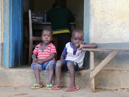 Two young boys sit outside a primary school classroom