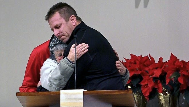 Brandon Luft is hugged as he begins to speak on Wednesday during a vigil at St. Stephen Lutheran Church in Liberty, Mo, for his wife, two of his daughters and a friend of the family who were killed in a car crash the day after Christmas on icy roads near Abilene, Kan. Sisters, Brianna and Aria Luft, their mother, Lisa Luft and Brianna's friend, Saleena Senzee, were killed.
