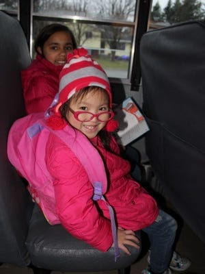 Weston Elementary students look at a book while riding the bus.