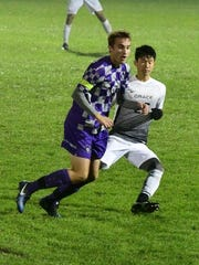Goshen College's Spencer Aeschliman (left) vies for the ball.