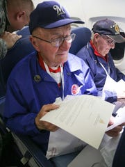 Lee Roy Wagner reads letters during Mail Call on the return trip from Washington, D.C., to Milwaukee on a Stars and Stripes Honor Flight in November 2015.