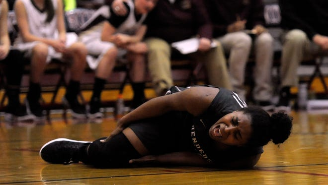 Henderson County's Alisha Owens winces in pain as the Webster County players and coaches watch in the background in the first half Saturday, March 4, 2017, night during the Kentucky High School Athletic Association's Second Region Tournament championship game at Hopkins County Central High School in Mortons Gap, Ky.